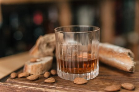 Glass with whisky on wooden board