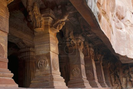 Cave 3: Pillared verandah or facade. Badami Caves, Karnataka, India. IT is 70 feet, 21 m, in length with an interior width of 65 feet, 20 m, Each column and pilaster is carved with wide, deep bases crowned with capitals that are partly hidden by brac