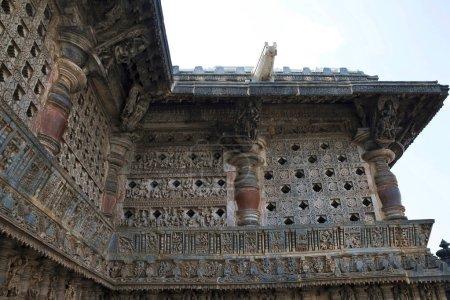 Ornate perforated window and Madanikas, Salabhanjika meaning celestial damsels, on top of the pillars. Chennakeshava temple, Belur, Karnataka, India