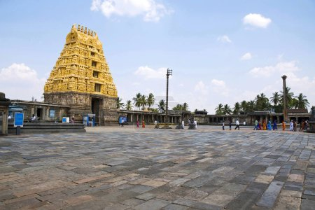 BELUR, KARNATAKA, INDIA, May 2016, Tourist, visitors at South East courtyard, Chennakeshava temple complex, from left, East Gopuram at the entrance, Flag post, Dhwajastambha and lamp post