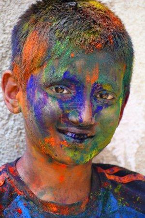 Photo pour Jeune garçon célébrant le festival Holi avec de la poudre colorée sur le visage, Yerawada Pune, Maharashtra, Inde - image libre de droit