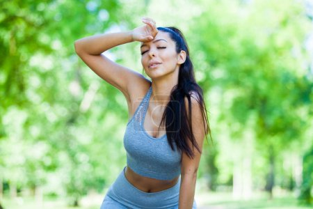 Young fit and tired beautiful girl resting after exercising outdoor during summer sunny day