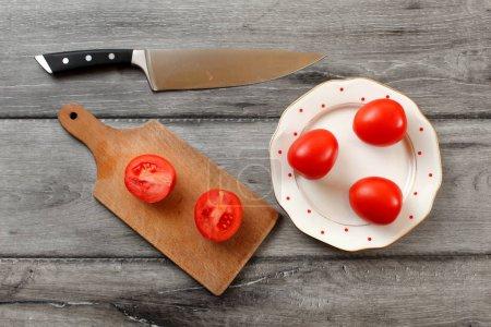 Photo pour Vue de dessus de table sur les trois tomates sur plaque de porcelaine blanche avec des points rouges, planche avec tomate coupée à moitié à côté de lui, couteau de chef portant également sur le bureau bois gris. - image libre de droit