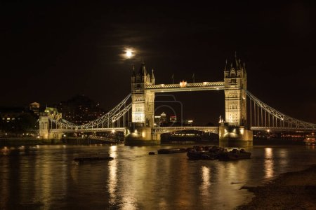 Photo for Tower bridge, full moon above, with river Thames illuminated in the night. London, United Kingdom - Royalty Free Image