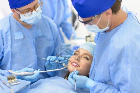 Photo pour Médecin dentiste et son équipe soignant un patient à la clinique - image libre de droit