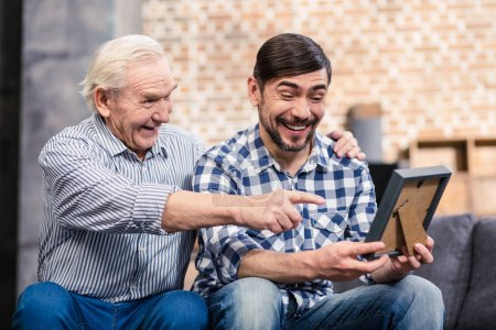 Photo for Full of joy. Cheerful father and son looking at a photo frame and smiling - Royalty Free Image