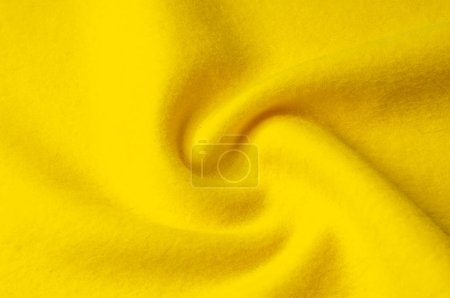Texture background pattern. Woolen yellow fabric, cloth for a blanket, outer clothing.  Closeup horizontal fragment