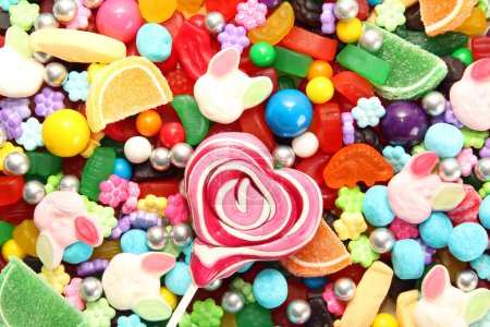 Photo for Assorted variety of sweet sugar candies includes lollipops, Easter bunny jelly, gummy bears, gum balls and sugar fruit slices. Candy flat lay background. - Royalty Free Image