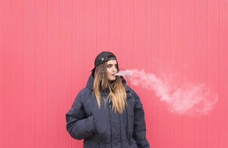 Young pretty girl with electronic cigarette...