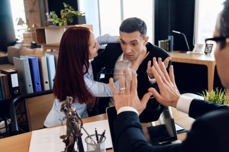 Enraged wife strangling husband sitting at divorce lawyers table
