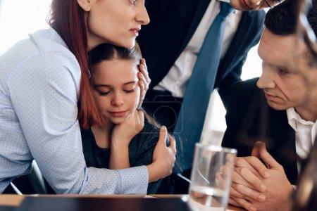 femme câlin pleurer fille tandis que l'homme en costume essayer de calmer mère et fille
