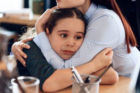 Jeune mère triste embrassant petite fille bouleversée assis dans le bureau d'avocat pour le divorce