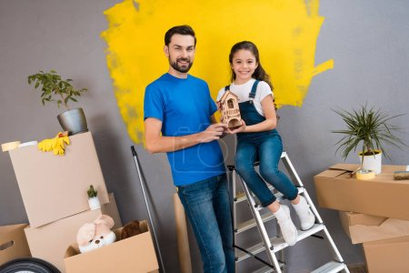 father and daughter holding toy house while family making repairs in new apartment