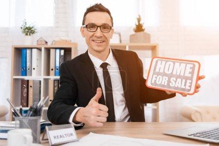 Photo pour Agence immobilière assis au bureau et tenant pancarte maison à vendre - image libre de droit