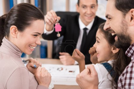 realtor giving to family keys of their new apartment