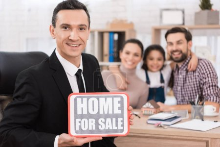 realtor holding sign home for sale in real estate agency
