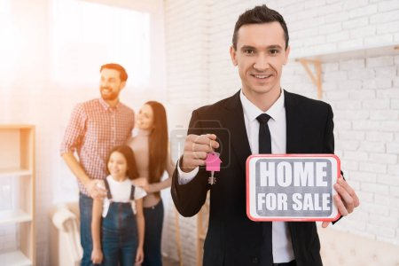 realtor holding sign home for sale and keys in real estate agency