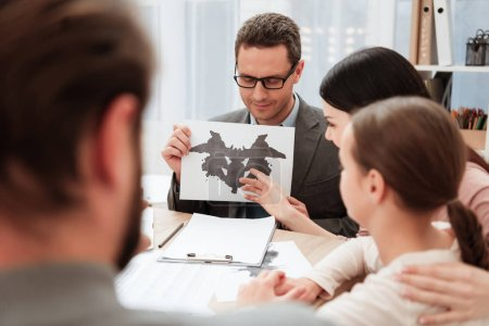 Little girl passing Rorschach test together with her parents in office of family psychologist