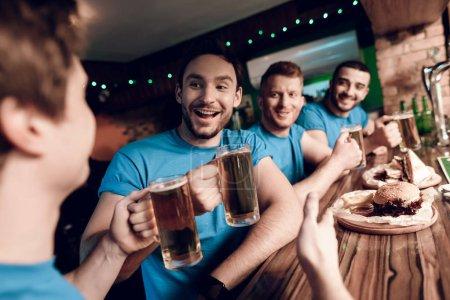 Photo pour Fans de football regarder le match boire de la bière et manger au bar des sports - image libre de droit