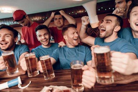Foto de Fans del equipo azul celebrando y brindando en el sports bar con opositores tristes en el fondo - Imagen libre de derechos