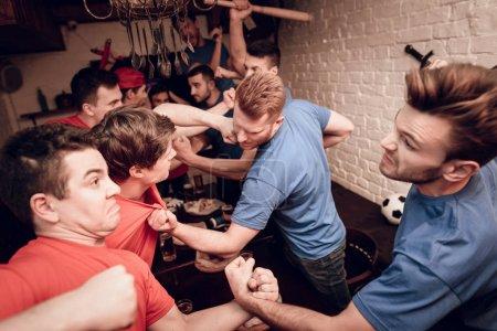 Photo pour Équipes rouge et bleus de fans hooligan au bar des sports de combat tout en regardant le match de football - image libre de droit