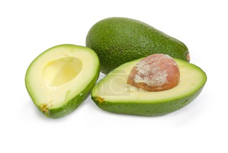 One green-skinned pear-shaped avocado cut in half and one whole avocado on a white background