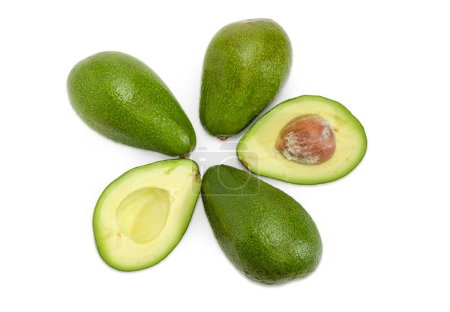 Top view of one green-skinned pear-shaped avocado cut in half and several whole avocados on a white background