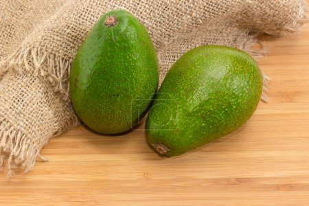 Two whole green-skinned pear-shaped avocado fruit on a wooden bamboo surface