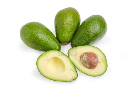 One green-skinned pear-shaped avocado cut in half and several whole avocados on a white background