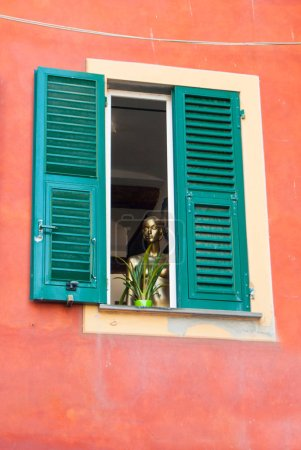 A woman's golden mannequin looks out of a window