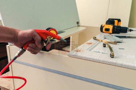 Photo pour Gros plan orange pistolet à air sur fond bois et autres outils - image libre de droit