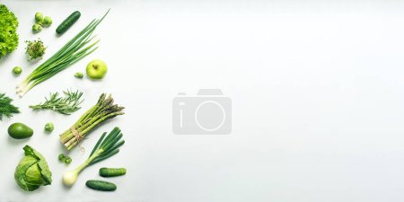Photo for Green vegetables wide flat lay concept. Microgreens, brussels sprouts, asparagus, rosemary, avocado, onion, cabbage and cucumber on white background, top view - Royalty Free Image