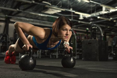 Photo for Life of fitness. Attractive young gym fitness woman doing pushups with weights beautiful sportswoman doing crossfit workout pushups exercise with kettlebells copyspace sport lifestyle strength success - Royalty Free Image