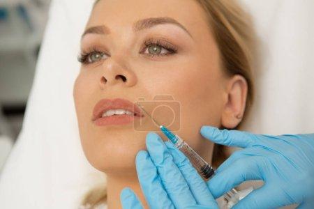 Photo pour Gros plan d'une femme magnifique recevant un traitement facial à la clinique de beauté. Esthéticienne professionnelle injectant du botox dans les lèvres d'une belle femme remplissante augmentation des lèvres chirurgie plastique cosmétologie - image libre de droit