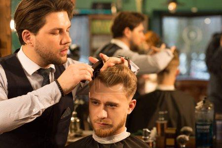 Photo pour Beau jeune homme souriant obtenir une nouvelle coupe de cheveux par un coiffeur professionnel au salon de coiffure copyspace service à la clientèle emploi coiffure coiffeur hipster masculinité toilettage mode . - image libre de droit