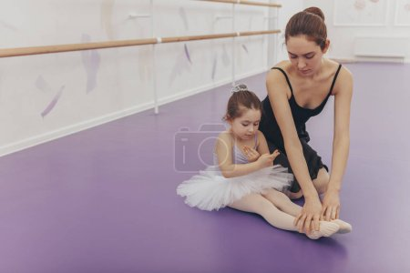 Cute little girl wearing tut and leotard, exercisi...