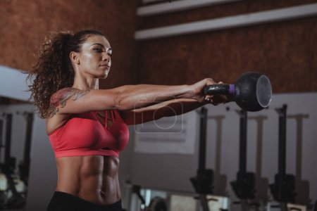 Photo for Attractive female crossfit athlete working out with kettlebell at the gym. Beautiful sportswoman with perfect fit body lifting kettlebell at crossfit box gym - Royalty Free Image