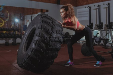 Photo for Stunning focused female crossfit athlete flipping huge heavy wheel, working out at crossfit box gym.Attractive sportswoman exercising at crossfit box gym - Royalty Free Image