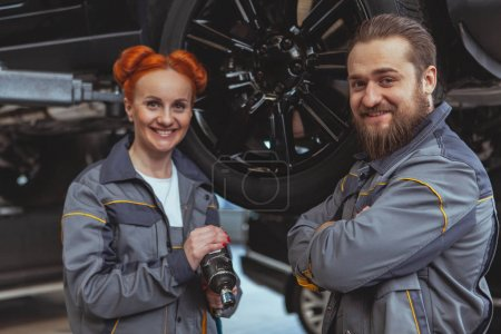 Photo for Cheerful beautiful female mechanic and her male colleague smiling to the camera, working at their car service station. Experienced car technicians repairing vehicles at the garage. Female equality concept - Royalty Free Image