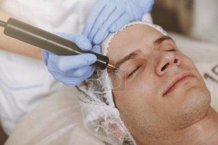 Photo pour Fermez vers le haut vers le haut d'un homme détendant à la clinique de soin de peau, recevant la thérapie microcurrente. Patient masculin obtenant le traitement facial par le cosmétologue professionnel. Concept de procédure anti-âge et de peau - image libre de droit
