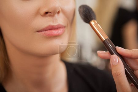 Photo for Cropped shot of a woman smiling while makeup artist applying highlighter on her face - Royalty Free Image