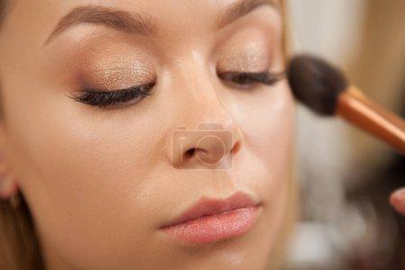 Photo pour Femme charmante se maquiller rofessional fait. Maquilleur appliquant surligneur sur les pommettes d'une femme magnifique - image libre de droit