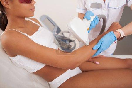 Photo pour Plan recadré d'une jeune femme africaine recevant un traitement d'épilation au laser par un cosmétologue professionnel - image libre de droit