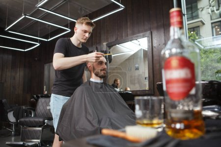 Professional barber looking concentrated, cutting hair of a male client, copy space
