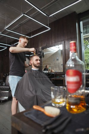 Vertical shot of a professional barber giving a new hairstyle to his male client