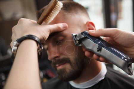 Photo pour Gros plan d'un homme se faisant raser la barbe par un coiffeur professionnel - image libre de droit