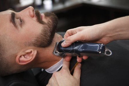 Cropped close up of a handsome bearded man getting his beard styled at the barbershop