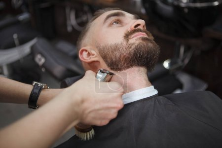 Cropped shot of a barber using electric clipper on the beard of male client