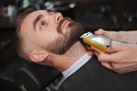 Close up of a handsome bearded man at the barbershop having his beard trimmed with electric clipper