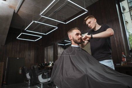 Attractive young man getting new haircut at the barbershop, copy space